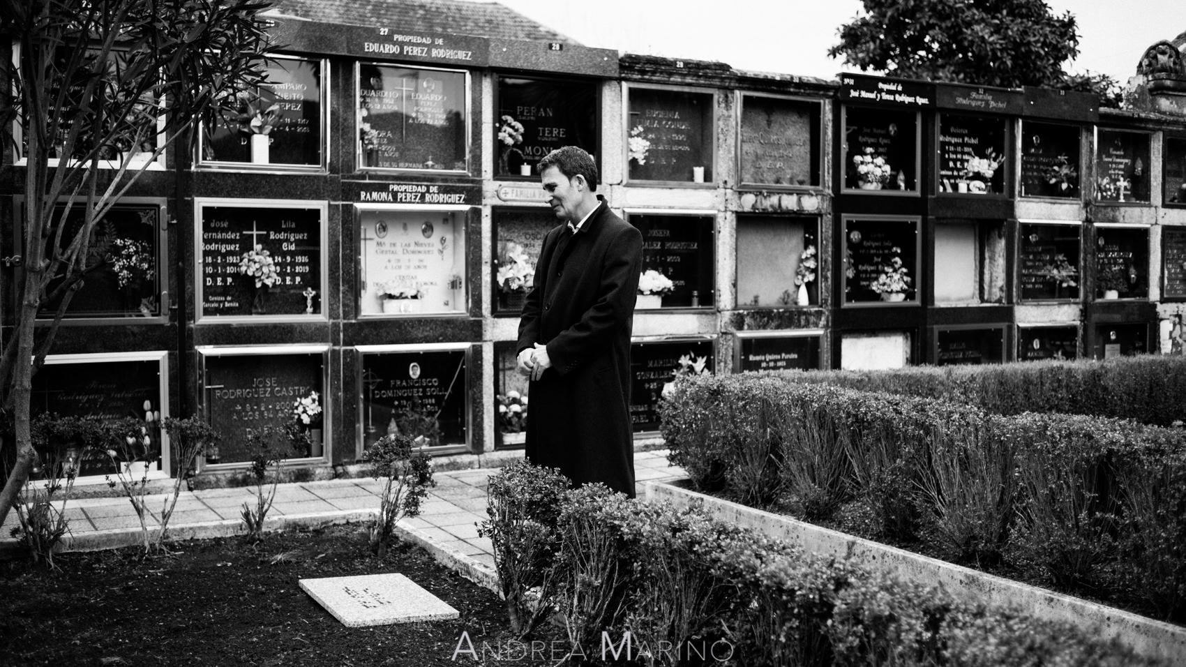 Actor delante de la lápida en el cementerio