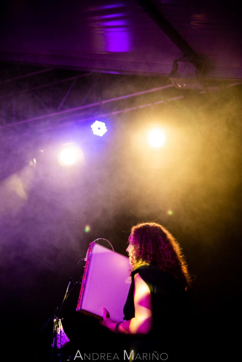 Cantante y percusionista envuelta en luz violeta y naranja
