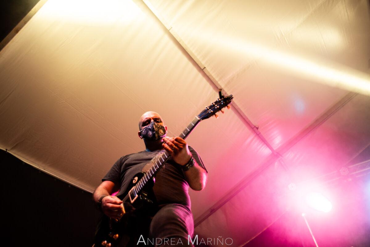 Guitarrista del grupo Motores con luz naranja y rosa