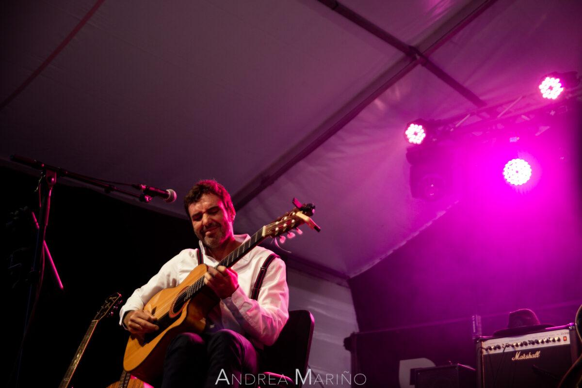 Guitarrista tocando envuelto en luz rosa